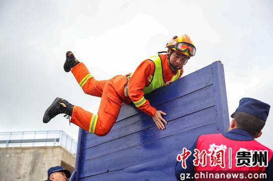 图为毕节支队消防指战员在100米消防障碍比赛中。