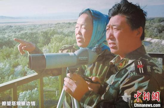 马军武夫妇在瞭望塔观察边情。(翻拍资料图) 戚亚平 摄