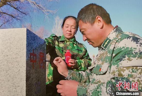 巡边途中,马军武夫妇为界碑描红。(翻拍资料图) 戚亚平 摄