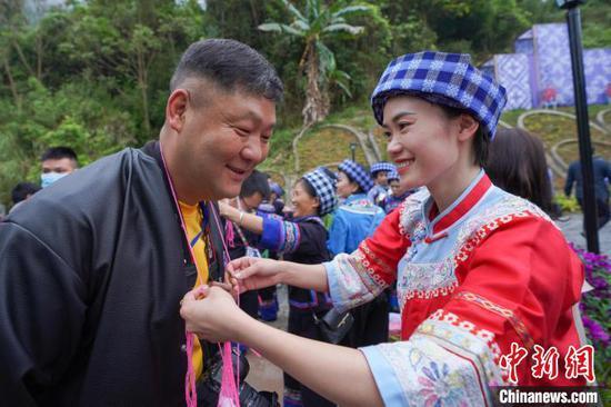 """图为布依族女青年给前来参加""""三月三""""文化节的客人赠送红鸡蛋,表示祝福。 贺俊怡 摄"""