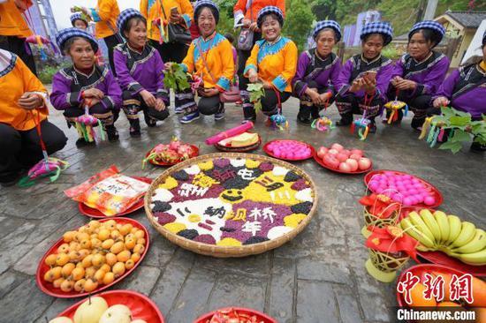 图为布依族妇女展示用于祭祀的花米饭。 贺俊怡 摄