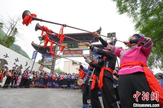 """图为布依族同胞在寨门吹奏唢呐和长号,欢度传统节日""""三月三""""。 贺俊怡 摄"""