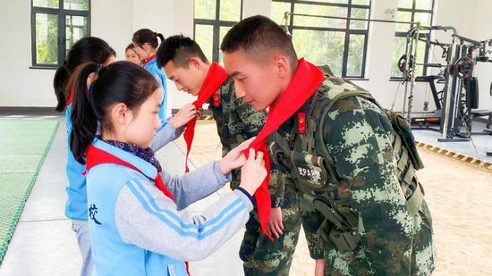 学生们为武警官兵代表戴红领巾  王鹏博 摄