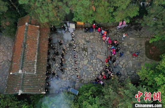 岜沙苗寨的村民在举行寨门迎宾仪式(无人机照片)。 吴德军 摄