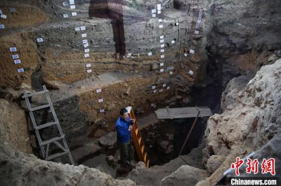 图为张兴龙站在被挖掘的8米深坑,其身旁的土层被标记成了25个地层。 瞿宏伦 摄