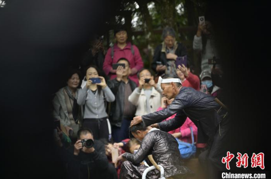 岜沙苗寨的村民在为游客展示镰刀剃头。吴德军 摄
