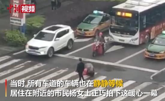 """暖心!男子护送""""蜗行""""残疾人过路 车辆安静让行"""