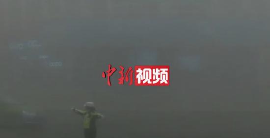 新疆:能见度30米 女交警雾中指挥
