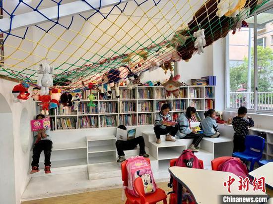 图为当地儿童在三宝儿童图书馆开馆当日看书学习。 张冬冬 摄