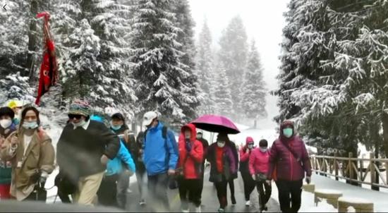 新疆天山天池游人踏雪寻春
