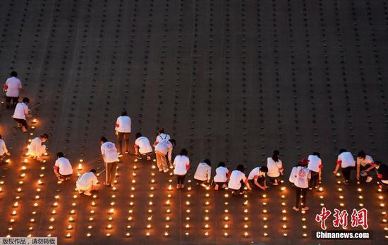 当地时间4月22日,泰国巴吞他尼府,志愿者和僧侣一起点燃33万根蜡烛打造坐佛图像,创造世界最大火焰图像吉尼斯世界纪录。