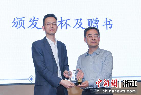 浙江大学创新创业学院常务副院长阮俊华为主讲嘉宾送上纪念奖杯。  王刚 摄