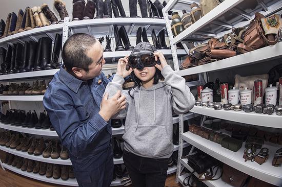 辛志强为前来参观的小学生试戴藏品。吴海燕 摄