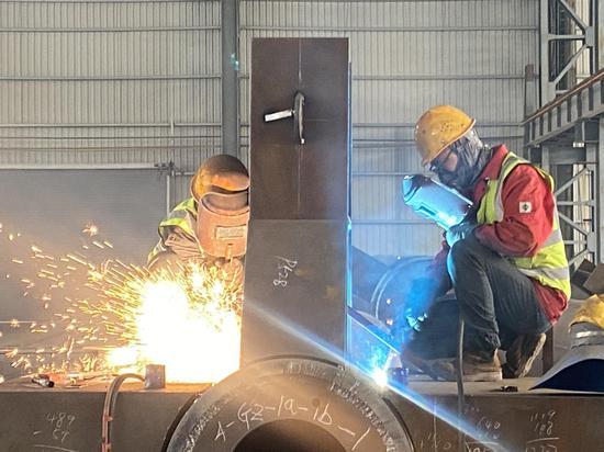 工人们在乌鲁木齐国际机场T4钢结构制作劳动竞赛中。