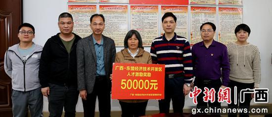 图为:广西-东盟经开区党工委、管委会为广西科学技术奖获得者送去奖励金潘志安 摄