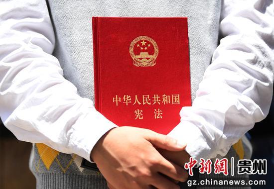 4月30日,在贵阳市南明甲秀高级中学成人礼仪式上,一名学生手握《宪法》读本。