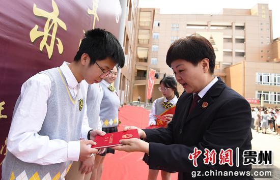 4月30日,在贵阳市南明甲秀高级中学成人礼仪式上,贵阳市南明区人民检察院的一名检察官正在向学生代表赠予《宪法》读本。