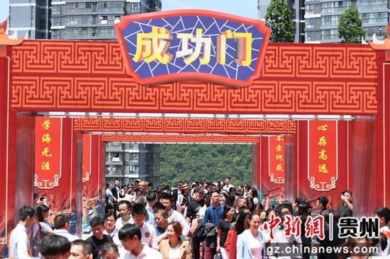 4月30日,在贵阳市南明甲秀高级中学成人礼仪式上,高三学生和家长一起走过成功门。