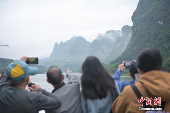 图为游客拍摄漓江山水风光。中新社记者 俞靖 摄