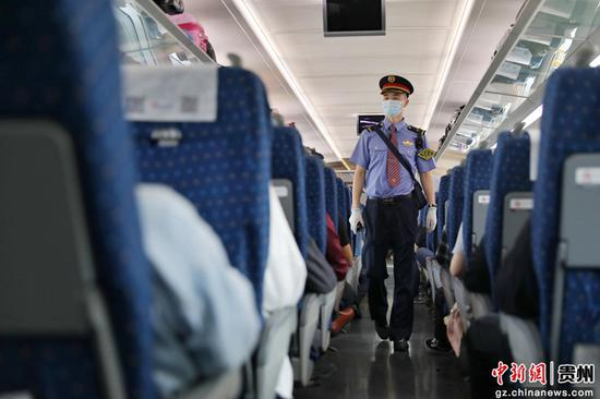 图为G1332次列车列车长候渊在车厢内巡视。 瞿宏伦 摄