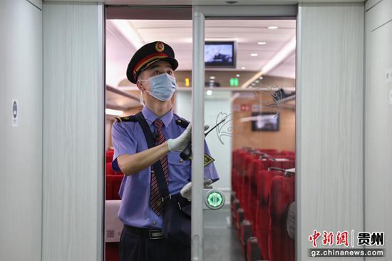 图为G1332次列车列车长候渊在检查车厢门感应状态。 瞿宏伦 摄