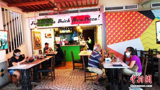 """当地时间5月1日,菲律宾首都马尼拉CBD马卡蒂绿带商圈一咖啡厅开始有限度接待 堂食客人。为控制疫情,5月1日至5月14日菲律宾首都大马尼拉地区及邻近4省布拉干、甲米地、拉古那、黎刹,继续实施""""修订版加强社区隔离""""(MECQ)政策。同时,执行 MECQ地区餐饮业获准进一步开放运营,除了外卖、以30%客座外场供应餐食,即日起可以10%容量接待堂食客人。中新社记者 关向东 摄"""