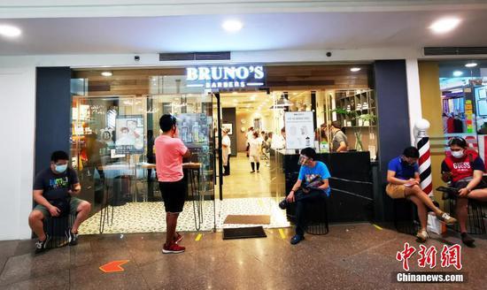 """当地时间5月1日,菲律宾首都马尼拉CBD马卡蒂绿带商圈一美容美发店以30%容量复业,客人在店外排队等候叫号。为控制疫情,5月1日至5月14日菲律宾首都大马尼拉地区及邻近4省布拉干、甲米地、拉古那、黎刹,继续实施""""修订版加强社区隔离""""(MECQ)政策。同时,执行MECQ地区美容美发业获准有限度复业。中新社记者 关向东 摄"""