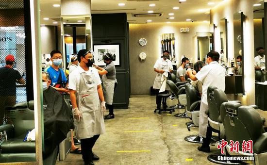 """当地时间5月1日,菲律宾首都马尼拉CBD马卡蒂绿带商圈一美容美发店以30%容量复业。为控制疫情,5月1日至5月14日菲律宾首都大马尼拉地区及邻近4省布拉干、甲米地、拉古那、黎刹,继续实施""""修订版加强社区隔离""""(MECQ)政策。同时,执行MECQ地区美容美发业获准有限度复业。中新社记者 关向东 摄"""