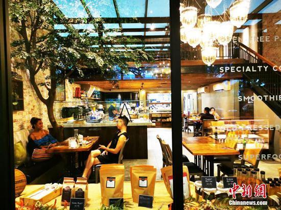 """当地时间5月1日,菲律宾首都马尼拉CBD马卡蒂绿带商圈一咖啡厅开始有限度接待堂食客人。为控制疫情,5月1日至5月14日菲律宾首都大马尼拉地区及邻近4省布拉干、甲米地、拉古那、黎刹,继续实施""""修订版加强社区隔离""""(MECQ)政策。同时,执行MECQ地区餐饮业获准进一步开放运营,除了外卖、以30%客座外场供应餐食,即日起可以10%容量接待堂食客人。中新社记者 关向东 摄"""