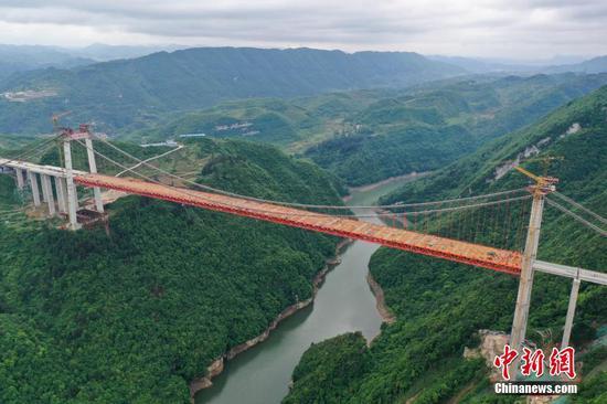5月4日,建设中的阳宝山特大桥。由中交二公局第二工程有限公司承建的贵州贵(阳)黄(平)高速公路阳宝山特大桥位于贵州省贵定县境内。该大桥全长1112米,主跨650米,是一座六车道钢桁梁悬索桥。(无人机照片) 中新社记者 瞿宏伦 摄