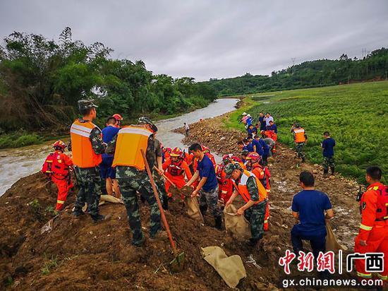 6月2日,武警官兵幫助村民裝填泥袋。李希樂 董亞濤  攝影報道