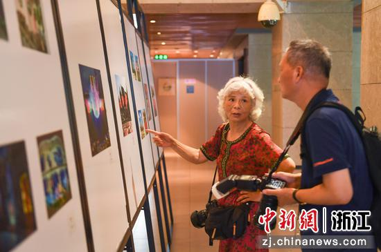 两位摄影爱好者在交流探讨展出的摄影作品。 王刚供图