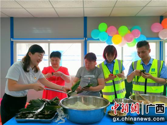 柳州德潤社區黨員教大家包粽子。謝夢玉 攝