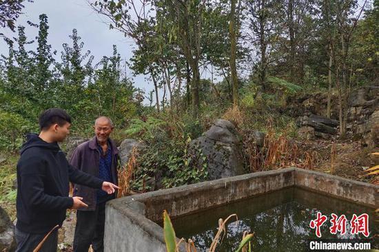 楊帆(左)在村民家查看用水情況(資料圖) 五峰縣委宣傳部 供圖