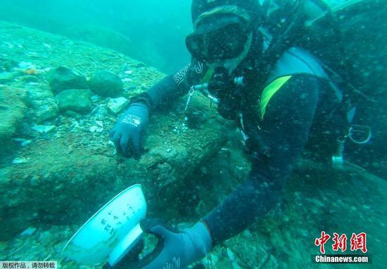 6月16日消息,兩艘具有歷史意義的古沉船在新加坡東部海域被發現,內有大量手工藝品,其中包括許多精美的中國14世紀青花瓷器。圖為潛水員展示瓷碗。