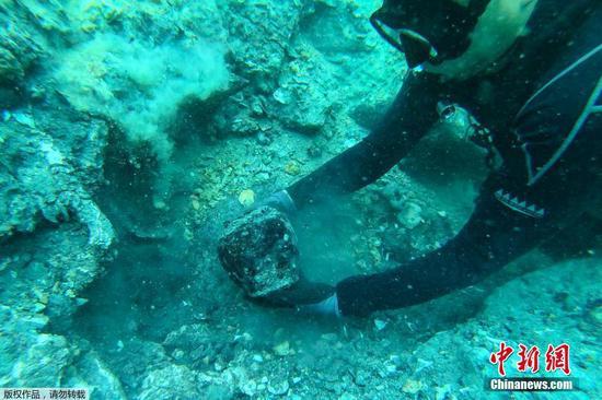 圖為潛水員打撈文物。