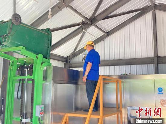 工人在北京市大興區清源街道棗園小區的垃圾站內進行廚余垃圾處理?!⌒戽骸z