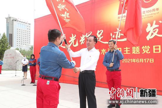 中國石油塔里木油田公司黨工委書記、總經理楊學文(中)為青年突擊隊授旗。陳士兵 攝