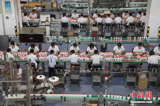2018年7月23日,贵州省仁怀市,贵州茅台酒厂的工人对茅台酒进行包装。2020年贵州茅台酒股份有限公司实现营业收入949.15亿元人民币,同比增长11.10%。 中新社记者 瞿宏伦 摄