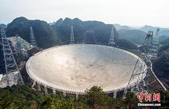 """2021年4月,位于贵州省平塘县大窝凼的世界最大的单口径射电望远镜""""中国天眼""""(FAST)向全球开放。FAST是目前世界上灵敏度最高的射电望远镜,配备的19波束L波段接收机,成为世界上最强大的脉冲星搜寻利器。自2016年9月落成启用以来,FAST团队发现脉冲星340颗。(2021年2月7日摄) 中新社记者 瞿宏伦 摄"""