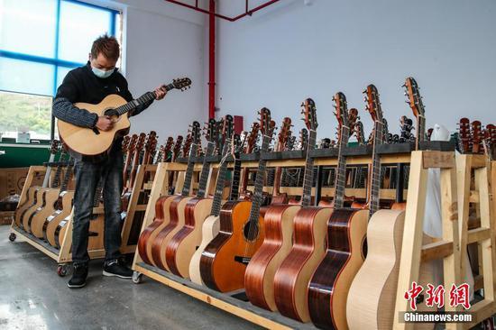2020年11月4日,贵州省遵义市正安县一家吉他企业的员工调试待出厂的吉他。2013年,昔日的贫困县正安通过招商引资和政策扶持,发展吉他产业,截至2020年底已有吉他生产及配套企业89家,年产吉他600多万把,全球销售的吉他中近一半产自这里,芬达、依班娜等世界顶级吉他品牌也从这里走出大山。 中新社记者 瞿宏伦 摄
