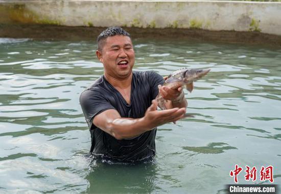村民正在捕鱼?!√普?摄