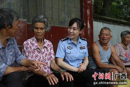 圖為民輔警向當地老人了解游擊隊員英雄事跡。甘勇 攝
