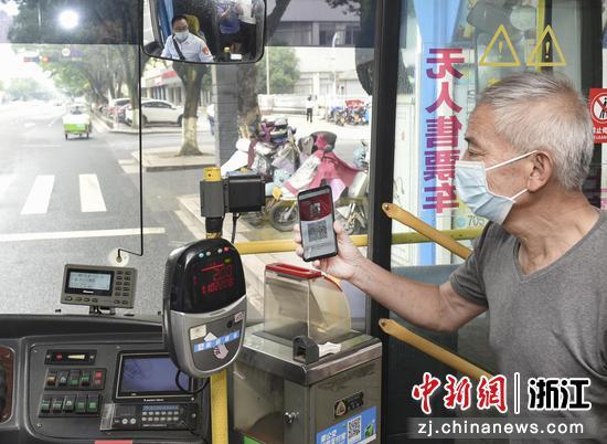 """一位老年人使用""""老年码""""乘坐公交车。 李建林 摄"""