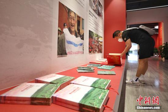 图为参观者在翻阅成就展展出的书籍。 瞿宏伦 摄