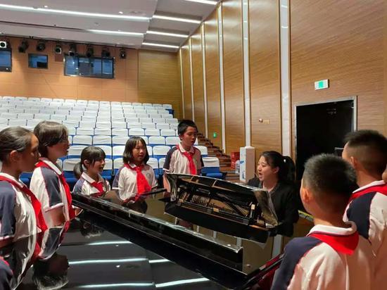 赵一阳教孩子们唱公益歌曲。