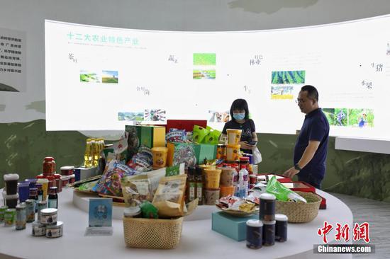 图为成就展展出的贵州扶贫产品吸引参观者。 瞿宏伦 摄