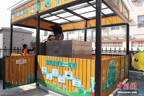 资料图:垃圾分类志愿者将厨余垃圾倒入厨余资源化一体机内。厨余垃圾经分解、压缩、发酵后可变为肥料。中新社记者 蒋启明 摄