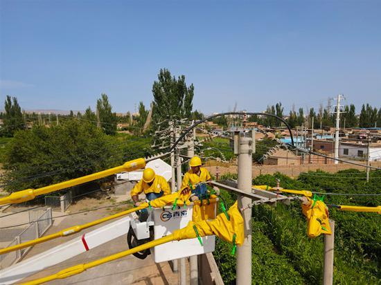 7月6日,国网吐鲁番供电公司带电作业人员阿里木·胡吉、开衣赛提 ·阿不拉冒着47摄氏度高温,在高昌区10千伏城南线1号杆开展带电作业,保障城区客户用电安全。谷碧娇 摄