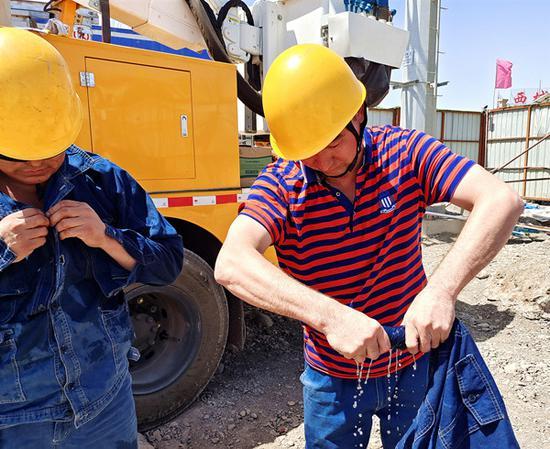 7月6日,国网吐鲁番供电公司带电作业人员阿里木·胡吉、开衣赛提 ·阿不拉冒着47摄氏度高温,在高昌区10千伏沙南二线22号杆开展带电作业工作。图为作业结束后阿里木·胡吉在拧干衣服汗水。刘栋 摄